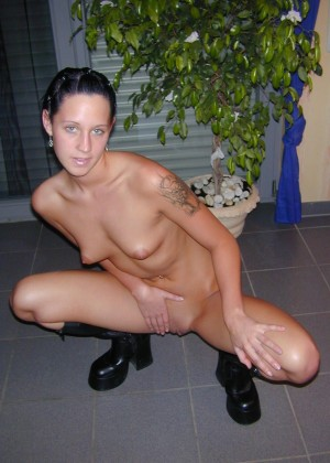 Naked short-haired brunette with a skinny ass in boots