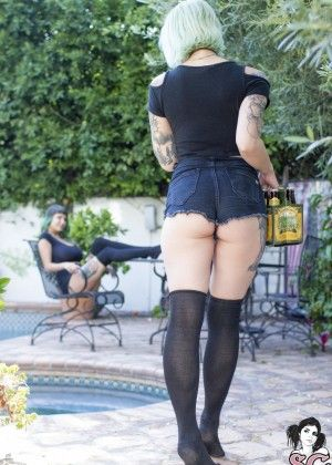 Tattooed chicks with beautiful asses are drinking beer in the pool