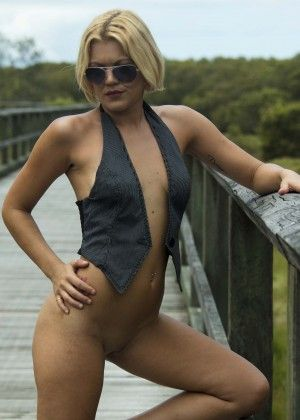 Woman with small breasts posing on a wooden bridge