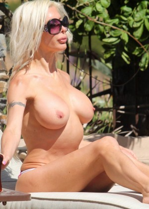 Mature glamorous French woman sunbathing topless