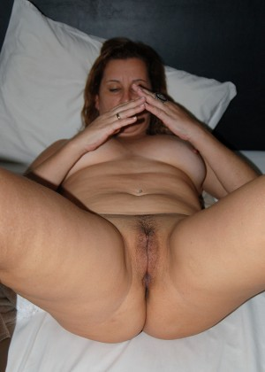 Lying in bed, the milf shows her cunt spreading her legs
